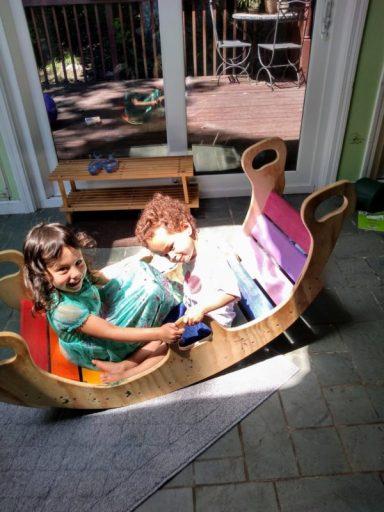 kids playing in a wooden rainbow rocker