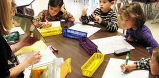 Kids around teachers desk