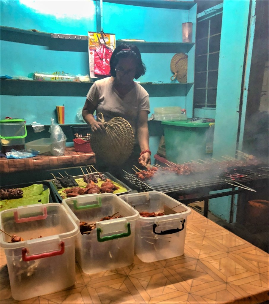 Lady cooking skewers in Manila