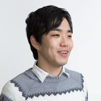 写真:白とグレーのセーターを着て、微笑む小林さん