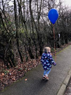 Happily walking with her balloon from Santa's elves