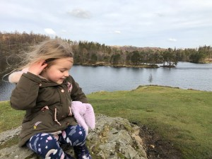 4 year old Spike enjoying a picnic overlooking Tarn Hows in the Lake District, Cumbria.