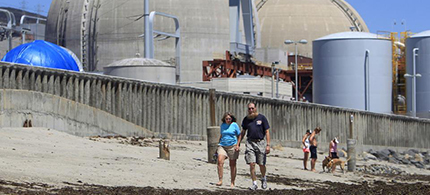 A couple walking on the sand in front of San Onofre nuclear plant. (photo: Lenny Ignelzi/AP)