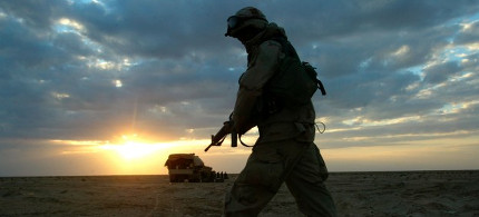 A soldier with A Company 3rd Battalion 7th Infantry Regiment walks through the desert near Karbala in central Iraq in 2003. (photo: AP)