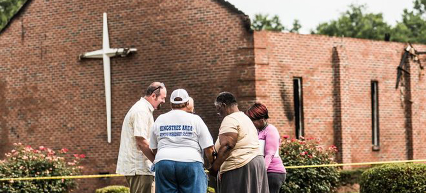 People pray near the burnt ruins of the Mt. Zion AME Church in Greeleyville, South Carolina. (photo: Getty Images)
