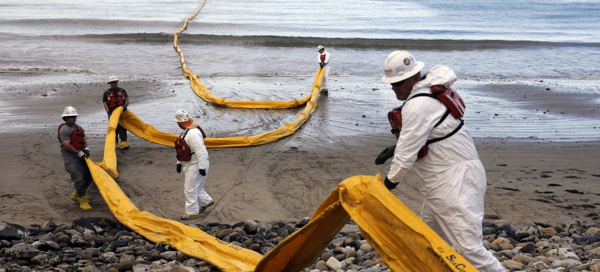 In this May 21, 2015, file photo, workers prepare an oil containment boom at Refugio State Beach, north of Goleta, Calif., two days after a ruptured pipeline created the largest coastal oil spill in California in 25 years. (photo: Jae C. Hong/AP)