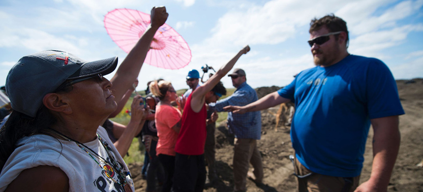 Protesters hold up their arms as they are threatened by private security guards near Cannon Ball, North Dakota, September 3, 2016. (photo: Robyn Beck/AFP)