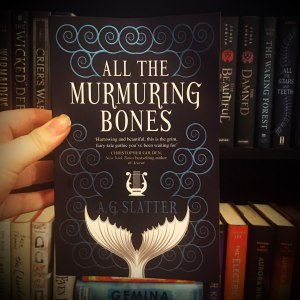 physical copy of All the Murmuring Bones held in front of bookshelves