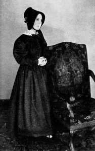 "Movie still of actress Mabel Ballin dressed as Jane Eyre, dark Victorian dress, standing by a chair, from 1921 movie ""Jane Eyre."""