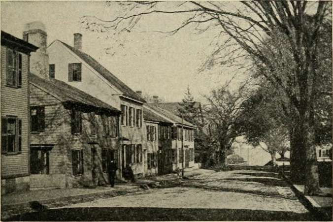 1917 Photo of Street in Salem, Massachusetts, suggesting what the town might have looked like in Hawthorne's Young Goodman Brown's day. Photo shows treelined street with New England 2-story style houses on left of the street. Black and White.