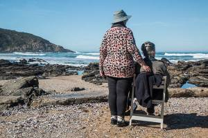 """Two older women at the right foreground are facing a beach with their backs to the camera. One sits in a chair and the other stands to her side with her hand resting on the chair back. """"Chair"""" and """"women"""" are concrete terms; """"friendship"""" is an abstract word."""