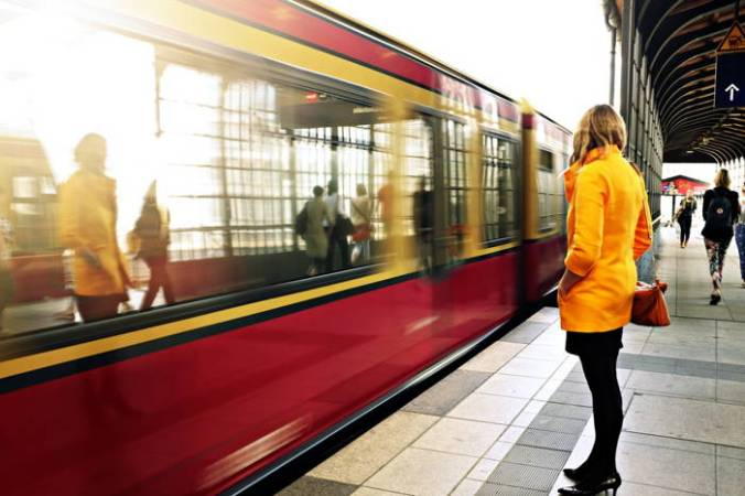 Shot of red train pulling into a station of the Paris Metro with woman in yellow jacket waiting.