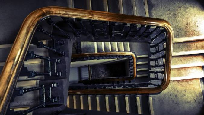 """Dark winding staircase shot from above brings to mind Hughes's """"Mother to Son"""" poem."""