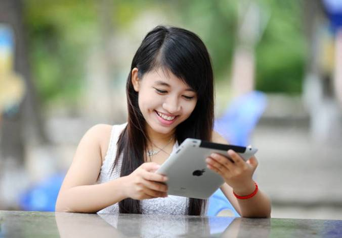 Girl with long dark hair is looking at an Ipad and smiling.