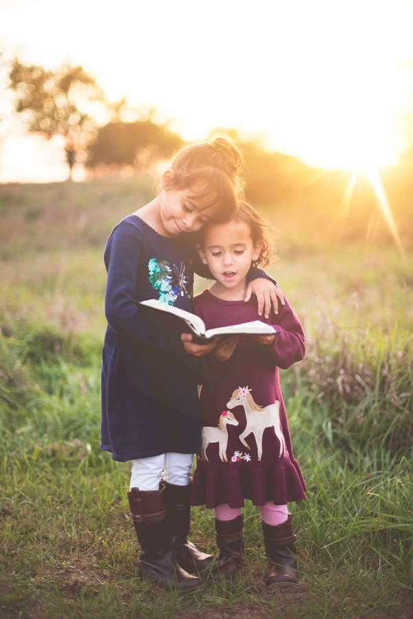 Two little girls stand in a field reading poetry from and open book.