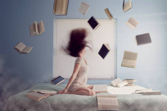 Girl sitting on bed with books whirling around her head.