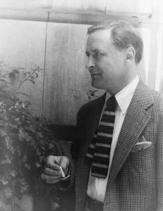 Photo of F. Scott Fitzgerald, in profile in front of fence, wearng striped knit tie and tweed jacket.