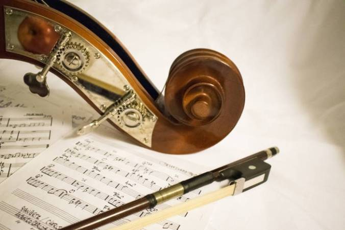 Photo showing scroll of violin and tip of a bow lying on a sheet of music.