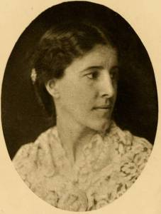 Old photograph-headshot of lady with dark hair and eyes with head turned far to her left, in a lace blouse.
