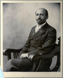 B & W Photo of African American gentleman sitting in a carved low-back wooden chair, early 19th century style suit and mustache.