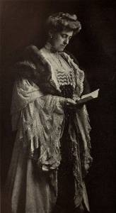Lady in elaborate Edwardian clothing, hair coiled in bun on top of head, cascading lace on sleeves, fur stole, holding and looking at a book.