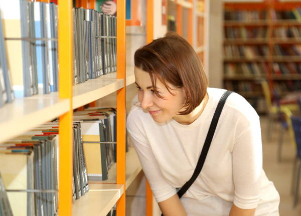 Young woman in white top leaning toward shelves of books in a library, gazing at a shelf and smiling.