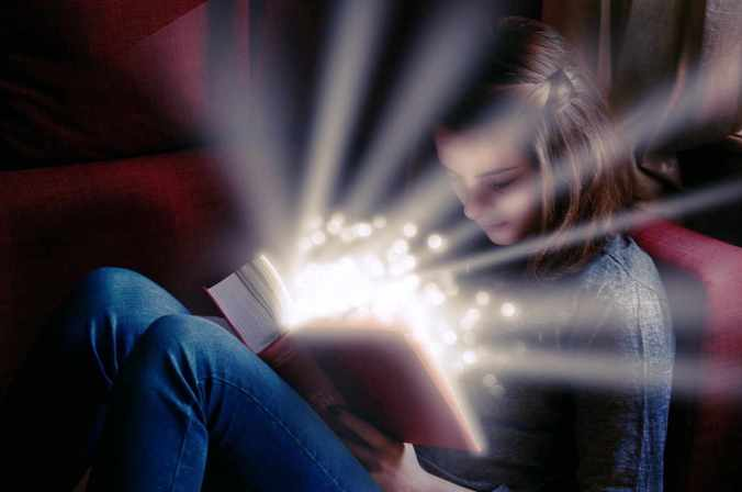 Photo showing girl intent on open book. From the pages a sparkly light is arising, suggesting that readers can be enchanted by plot but also gain a new view on the world.