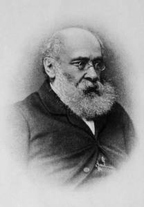 Victorian B & W headshot of gentleman with long shite beard and mustache, bald on top, white-haired, with small wire-rimmed glasses, 3/4 pose facing right.
