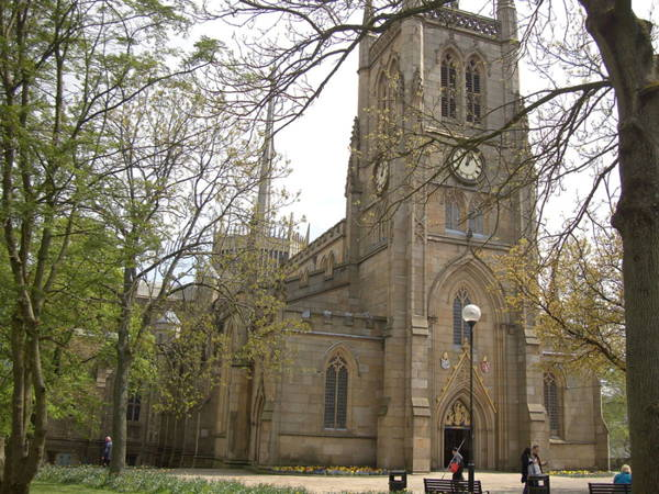 Color Photograph of symmetrical elevation of Blackburn Cathedral, yellow stone, tall bell tower in center, surrounded by trees.