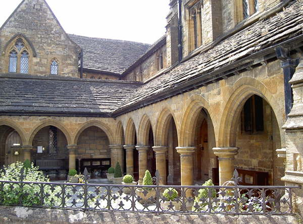 View of Medieval almshouses in yellow stone with roofed walk and row of arched supports.