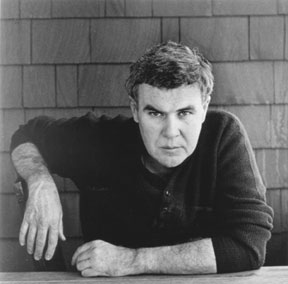 B & W Photo-man with wavy dark hair and intense serious expression leaning forward with one arm on table.
