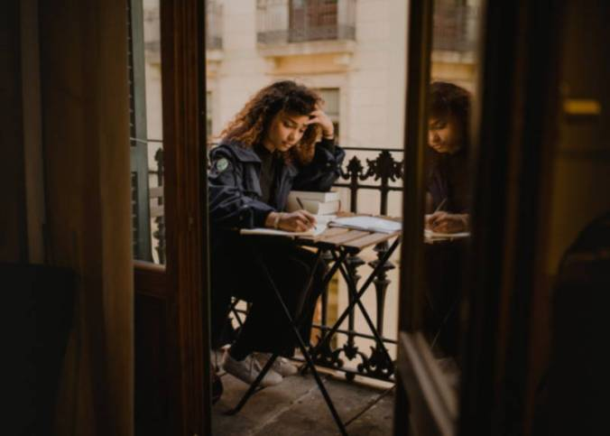 Young woman writing on small table, shown through open wooden door as she sits on a city balcony.
