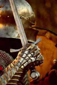 Close-up photo of knight in medieval armor, raising his sword in his right hand.
