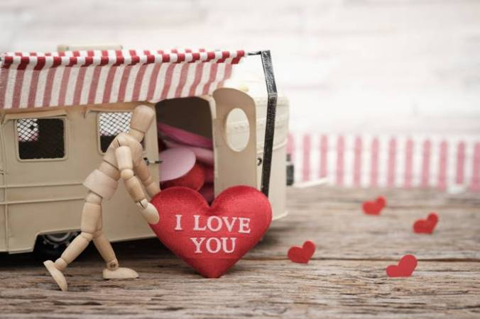 "Artist pose-able wooden figure rolls stuffed red heart toward mini caravan: Take a quick trip back down Love's highways and byways: re-sample ""All Kinds of Poems About Love."""