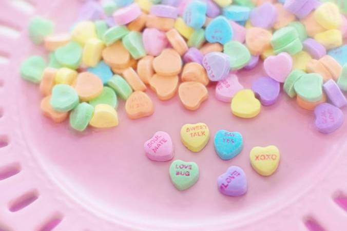 Pink plate showing several candy hearts with messages: Valentine Candy Heart message: Read some Great Literature about love!