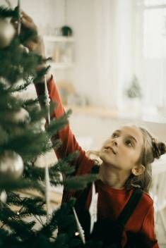 Little girl reaches up to place an ornament on a Christmas tree.