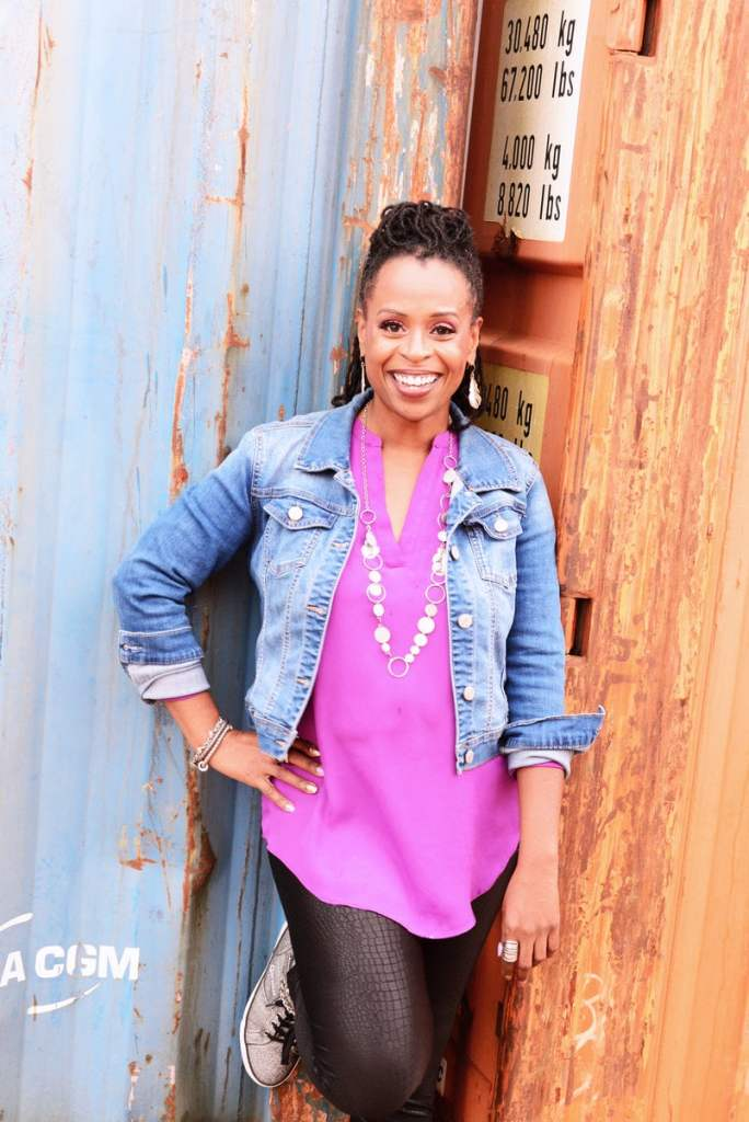 Black woman, author, Alicia D. WIlliams poses against a rust colored background