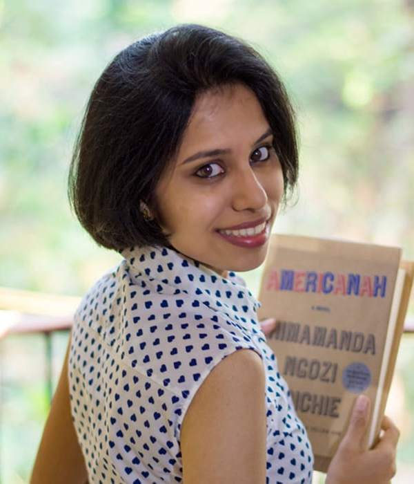 Indian woman holds novel, Americanah by Chimamanda Adichie