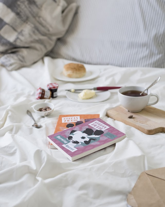 Books, a biscuit on a saucer, and a cup of tea res on a bed with white sheets