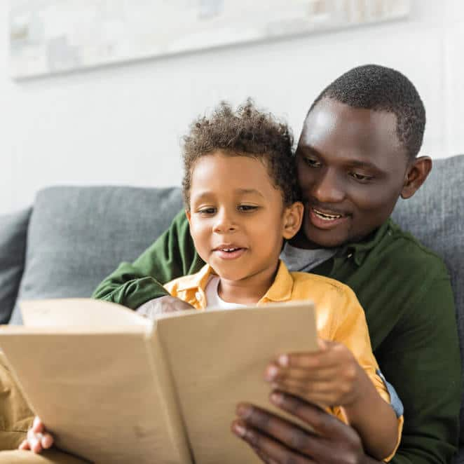 black father reading aloud to child on couch_cropped