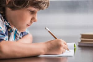 boy up close writing in notebook