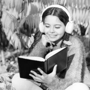 child reading and listening along to book outside_cropped