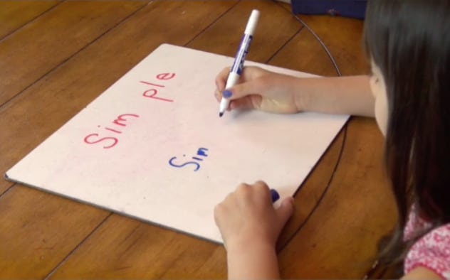 Multisyllable word reading practice on dry erase board