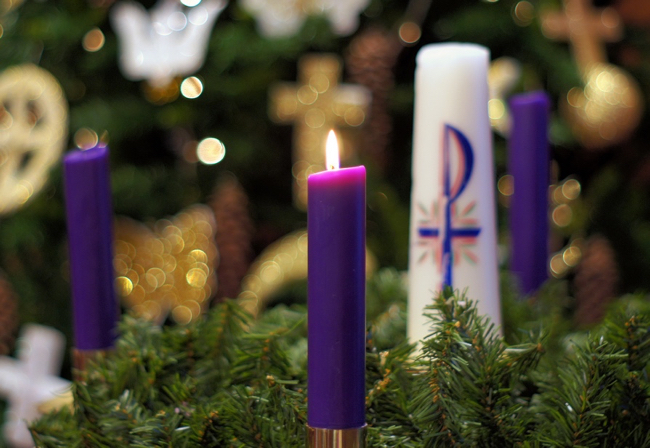 Purple candle lit, sitting in evergreen wreath with other candles