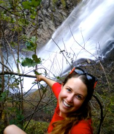 Gillian, wearing a red shirt and with sunglasses on her head, is looking at the camera while a waterfall cascades in the background