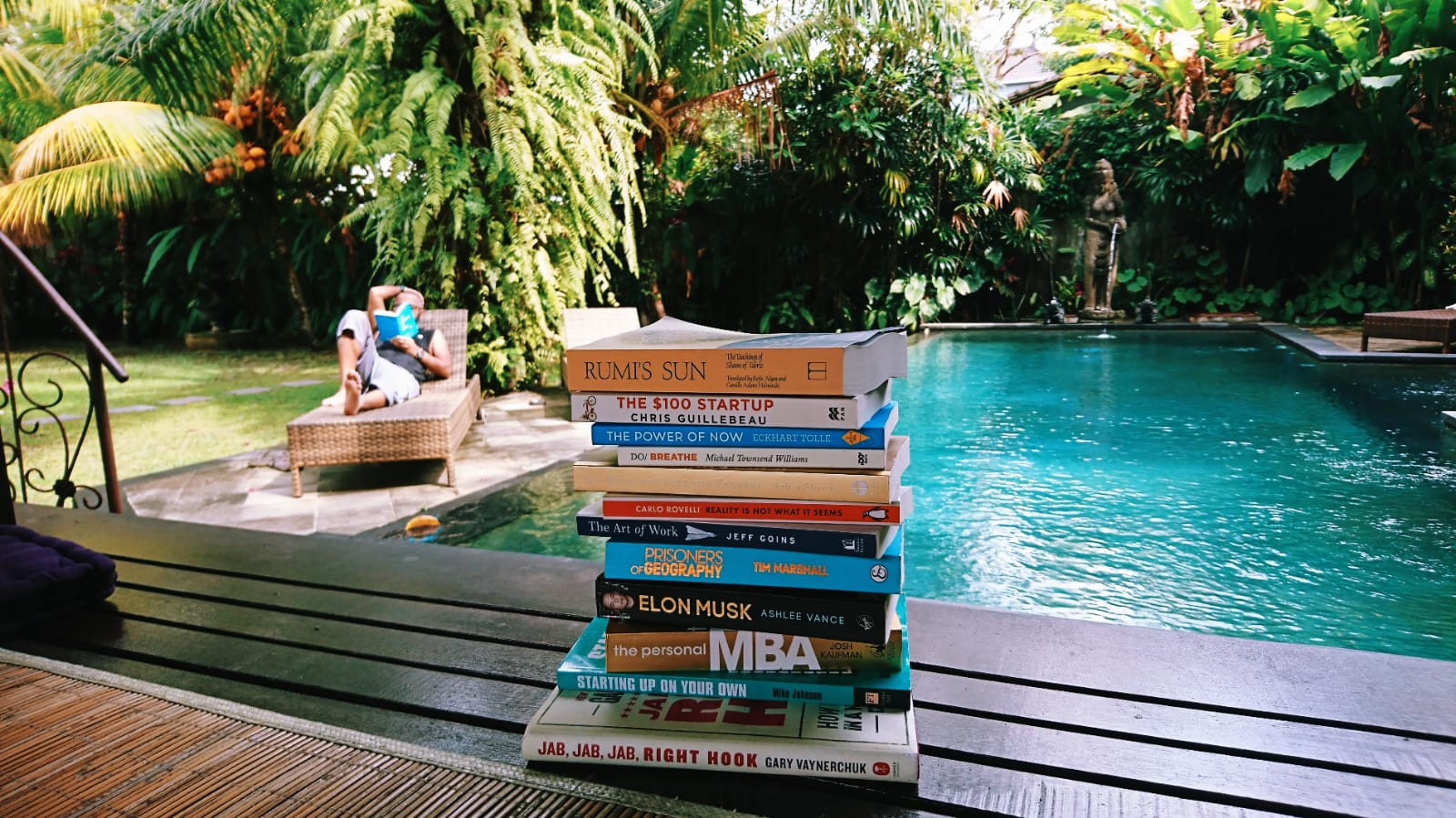 Read think and travel, a travel blog. A pile of 20 books for holidays in Bali, with a man reading a book near a swimming pool in the background