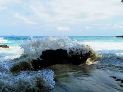 Blue Lagoon beach in Bali. Volcanic rock receiving a wave from the sea.