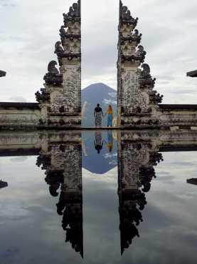 The heaven's gates at Pura Lempuyand, with the Mount Agung behind. Couple holding their hand while looking at the view.