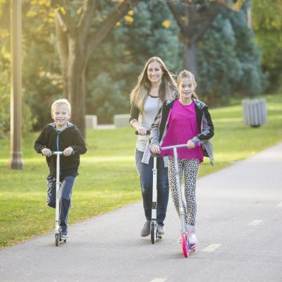 A women and her children riding together outdoors on a paved bike pathway. Smiling and having fun together at a outdoor nature park