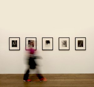 A blurred figure moves from left to right, with framed art photos in the foreground.